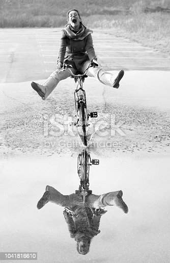 Ecstatic screaming mid adult woman cycling through puddle with reflection. Black and white development (RGB-File).