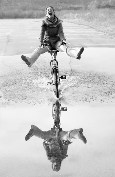 Ekstatische schreien Mitte Erwachsene Frau Radfahren durch Pfütze mit Reflexion – Foto