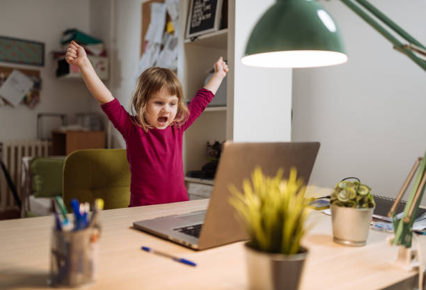 Ecstatic three year old girl celebrating winning on video game on laptop Cute three year old girl staying at home during COVID-19 lockdown and exploring new content on internet win stock pictures, royalty-free photos & images