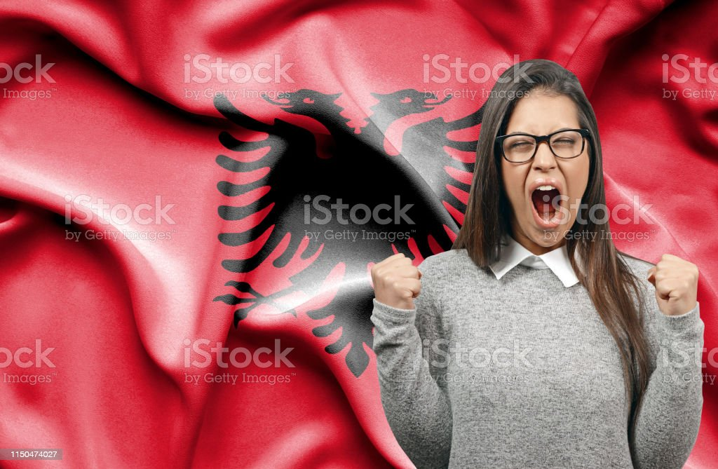 Ecstatic woman holidng fists and screaming against flag of Albania