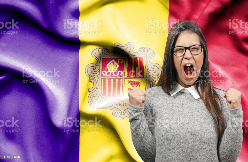 Ecstatic woman holidng fists and screaming against flag of Andorra