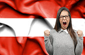 Ecstatic woman holidng fists and screaming against flag of Austria