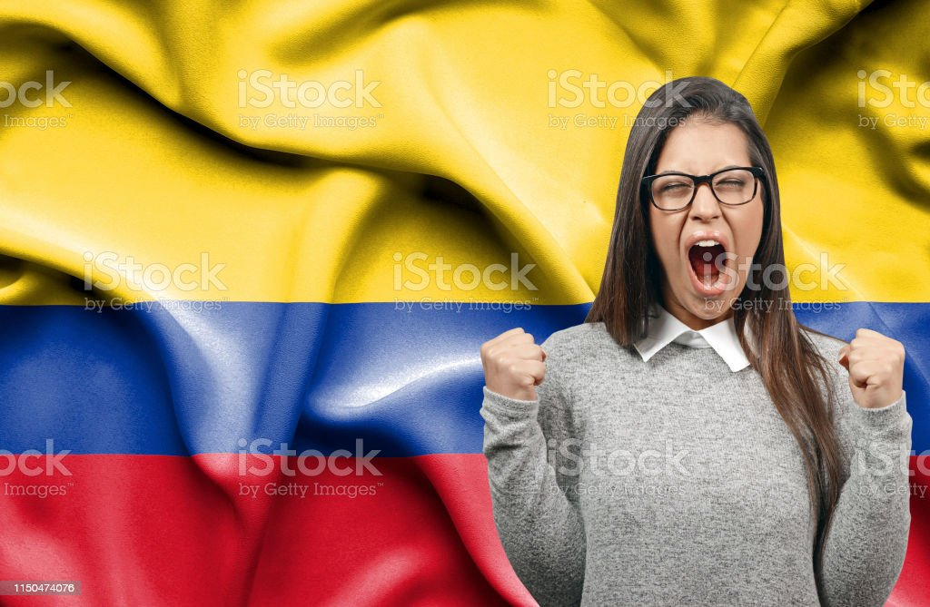 Ecstatic woman holidng fists and screaming against flag of Columbia
