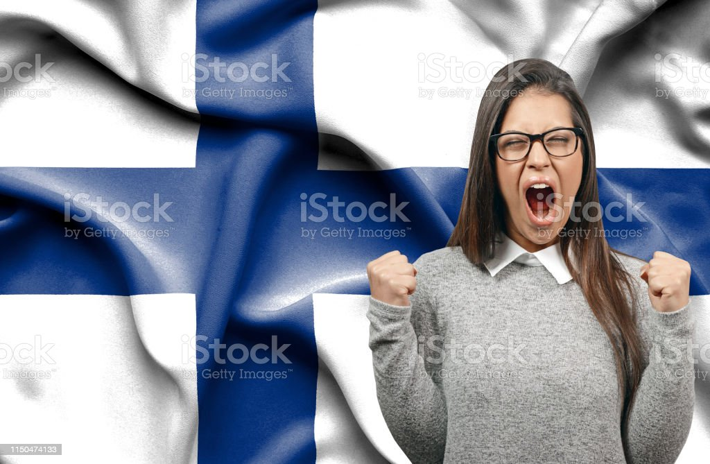 Ecstatic woman holidng fists and screaming against flag of Finland