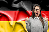 Ecstatic woman holidng fists and screaming against flag of Germany