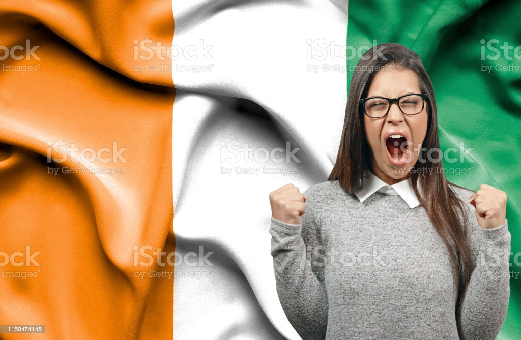 Ecstatic woman holidng fists and screaming against flag of Ivory Coast