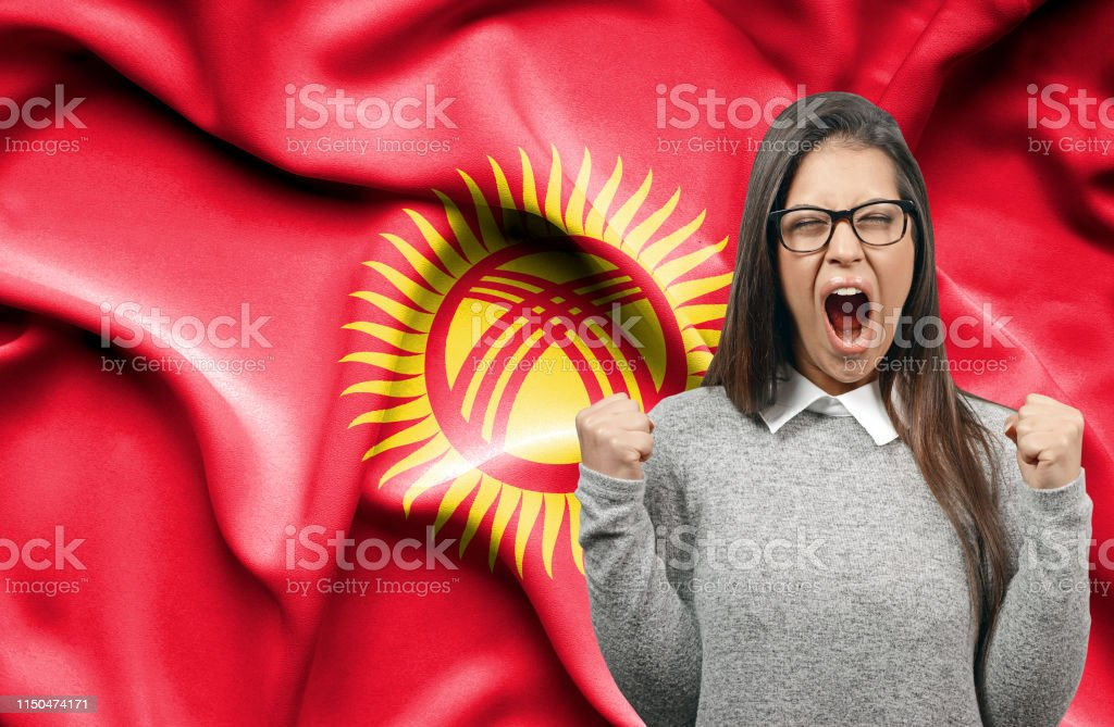 Ecstatic woman holidng fists and screaming against flag of Kyrgyzstan