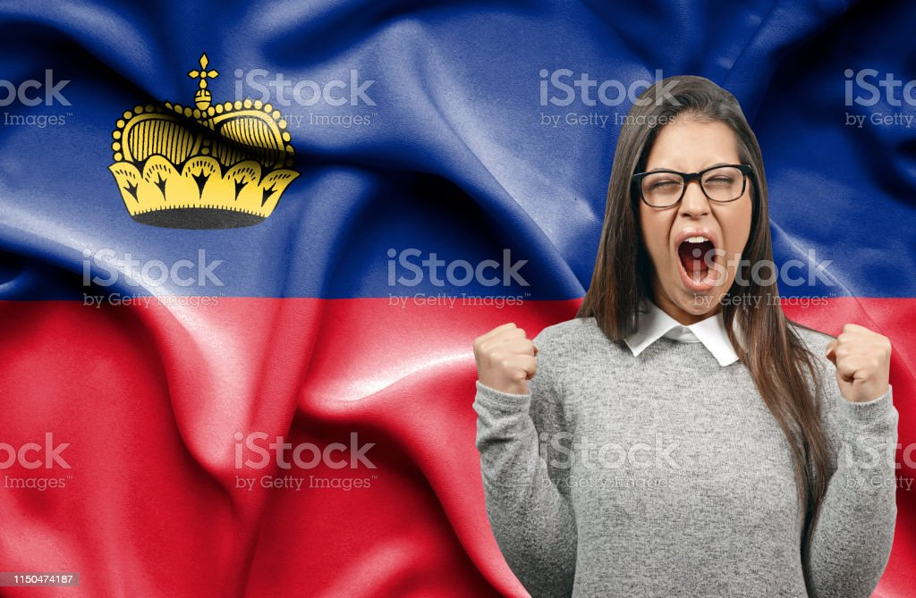 Ecstatic woman holidng fists and screaming against flag of...