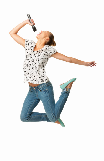 Full length of an ecstatic young woman singing into microphone. Vertical shot. Isolated on white.