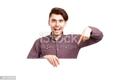 istock Ecstatic young man pointing down on blank  placard 497493588