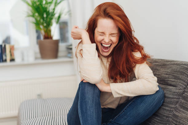 Ecstatic young woman cheering in jubilation stock photo