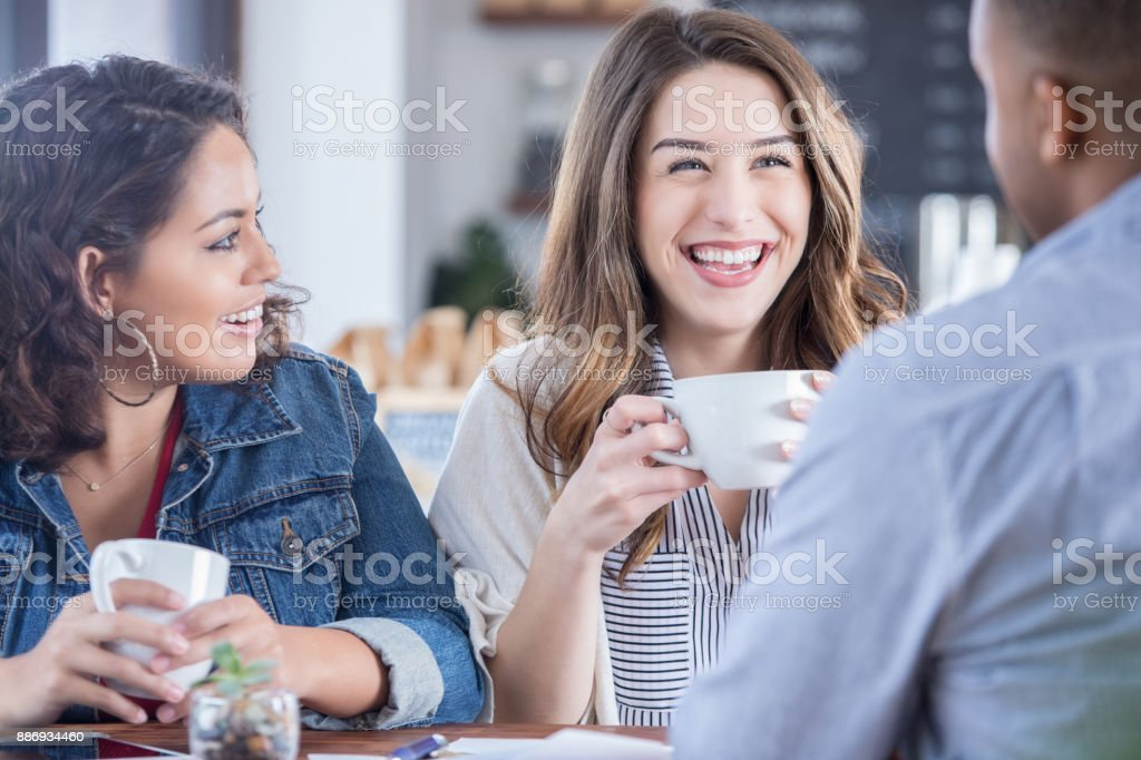 A young woman laughs as she sits with two friends at a table in a...