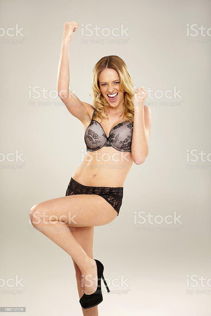 Portrait of ecstatic young woman wearing lingerie celebrating success...