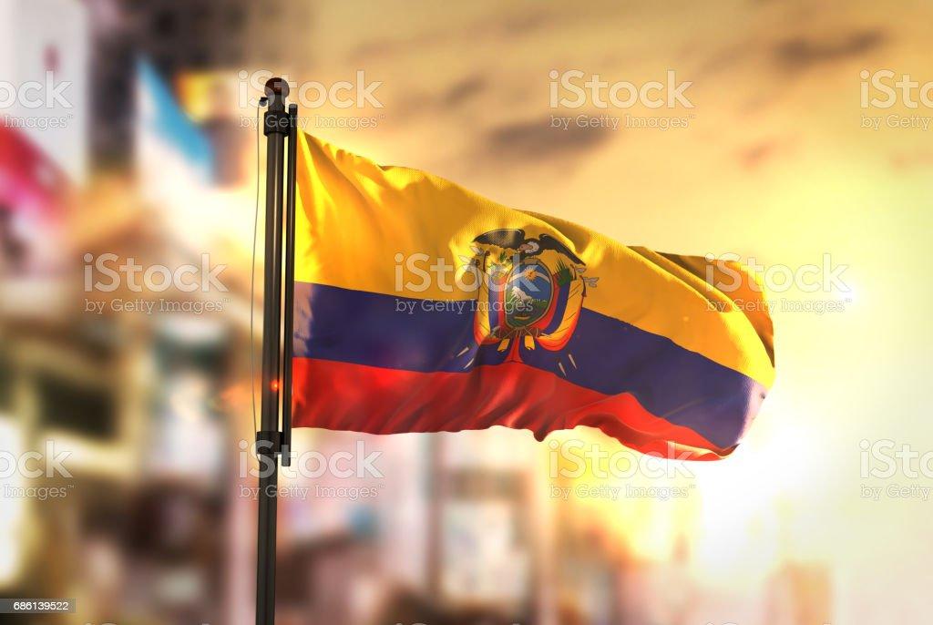 Bandera de Ecuador contra la ciudad borrosa de fondo en contraluz amanecer - foto de stock