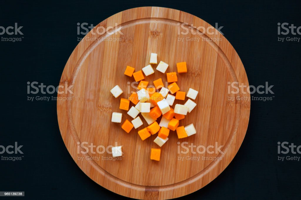 Edam and mimolette cheese on a round bamboo board on dark background, top view. From above. royalty-free stock photo