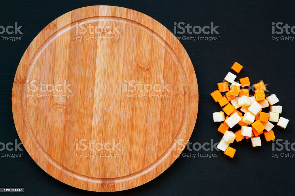 Edam and mimolette cheese with round bamboo board on dark background. Copy space, top view. Flat lay. zbiór zdjęć royalty-free
