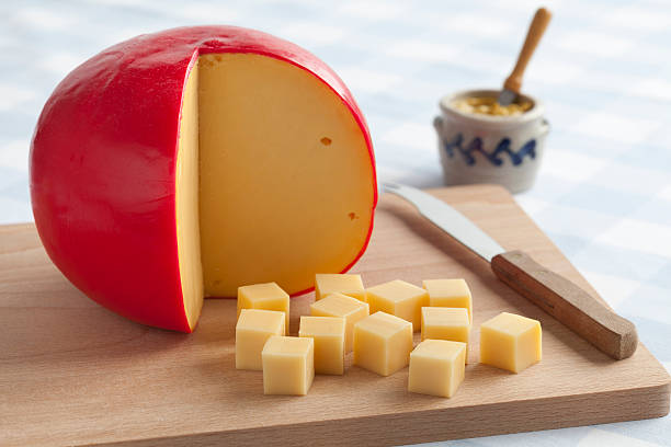 Edam cheese and cubes Edam cheese and cubes on a cutting board Edam cheese stock pictures, royalty-free photos & images