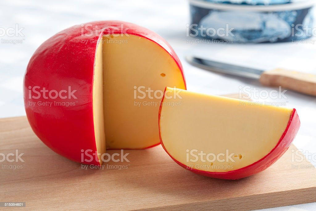Edam cheese on a cutting board stock photo