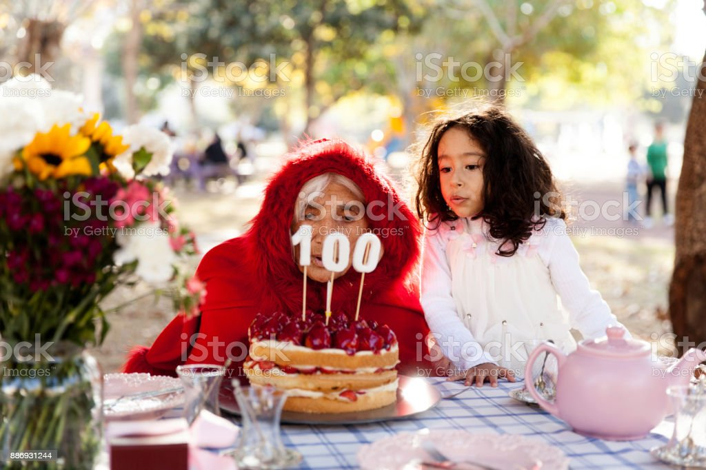 Ederly woman and grandson bowing birthday cake stock photo