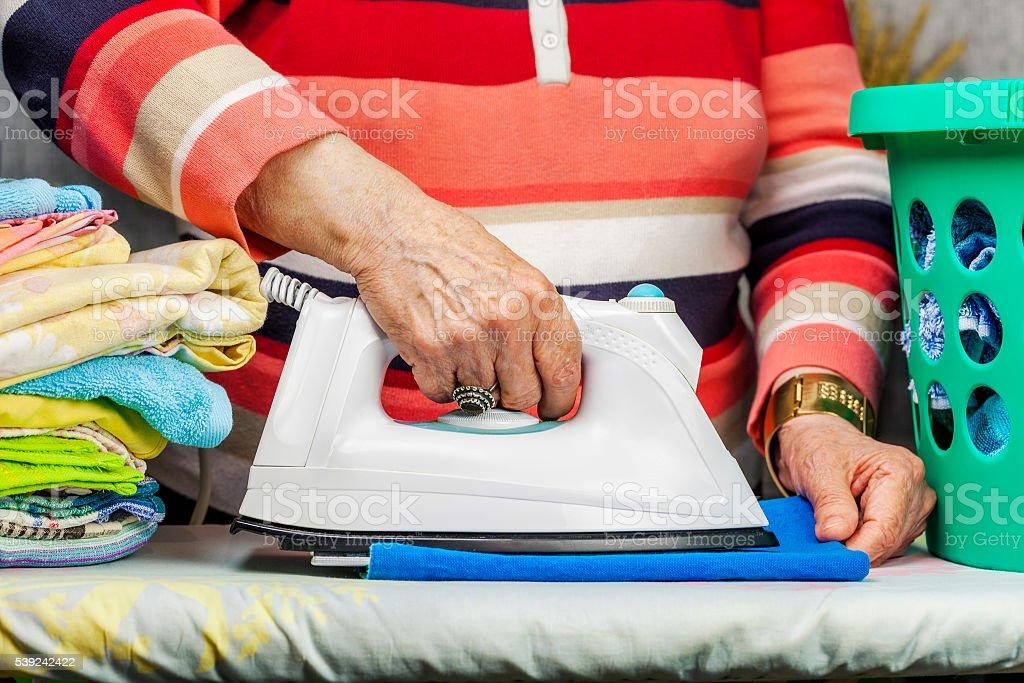 Ederly woman ironing foto de stock libre de derechos