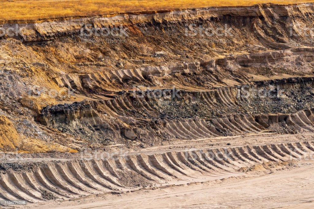 Kante einer Braunkohlemine mit Mustern im Boden aus der Schaufel des Umzugsbaggers – Foto