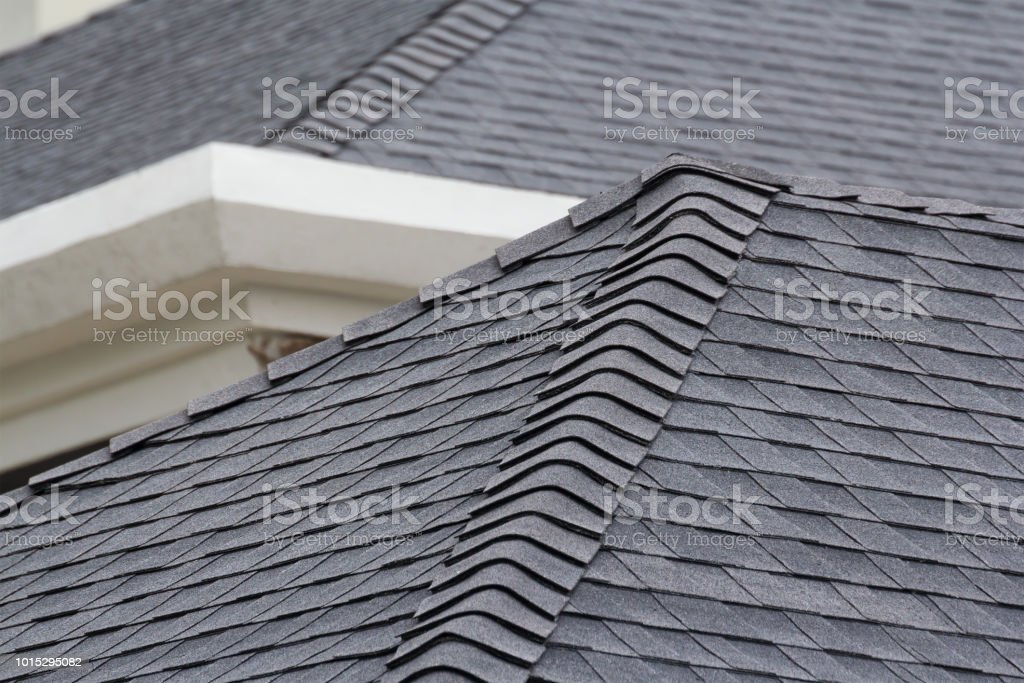 edge of Roof shingles on top of the house, dark asphalt tiles on the roof background. stock photo