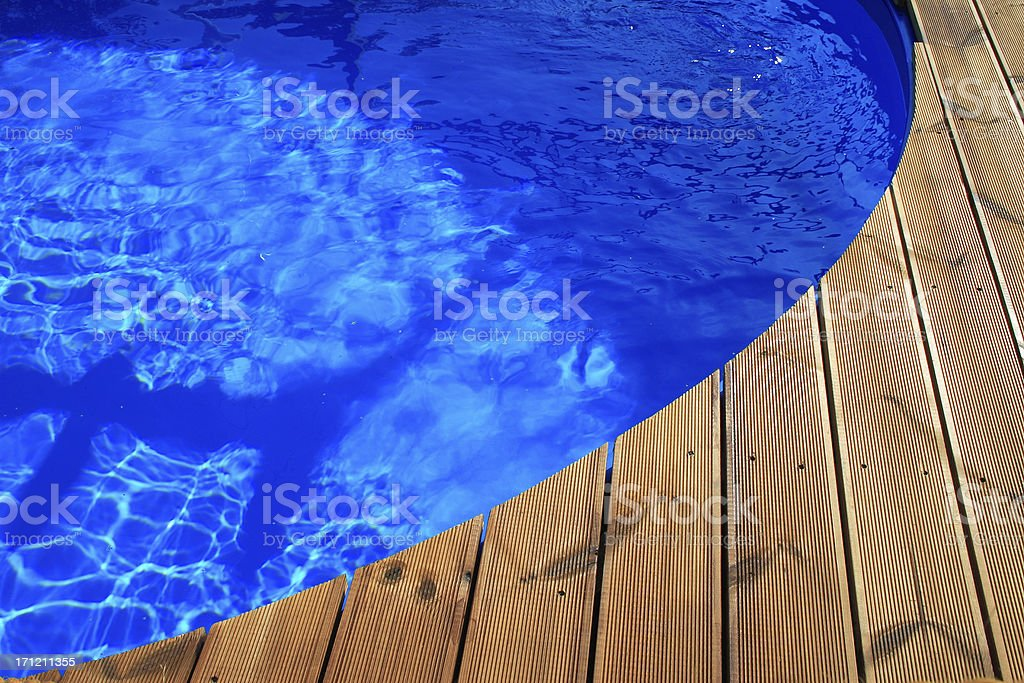 Edge of round blue swimming pool with wooden deck royalty-free stock photo