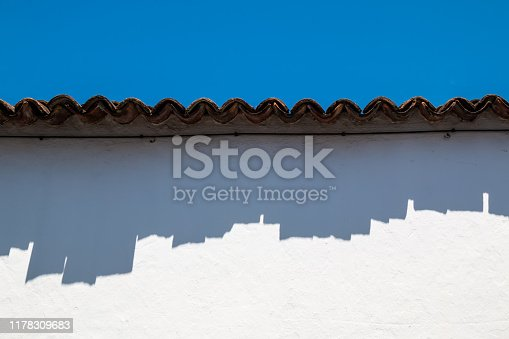 Wavy edge of a roof with its shadow on a white painted facade of a house. Bright blue sky. Ribeira Grande, Sao Miguel, Azores Islands, Portugal.