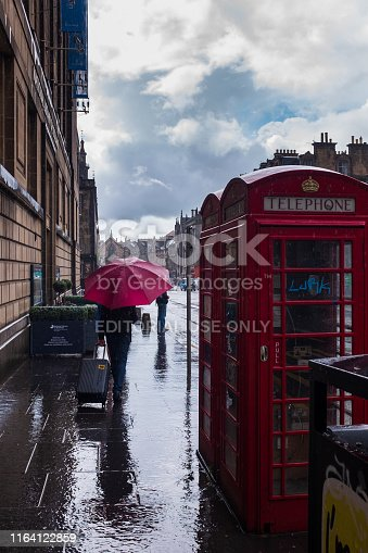 Edinburgh, Scotland - July 20, 2019: Characteristic telephone booth in the city center on a rainy day