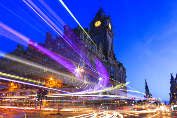 Edinburgh at night scene with Speed of Lights Edinburgh at night scene with Lights streak from high-sided vehicles on Princess street and Balmoral hotel on background princes street edinburgh stock pictures, royalty-free photos & images