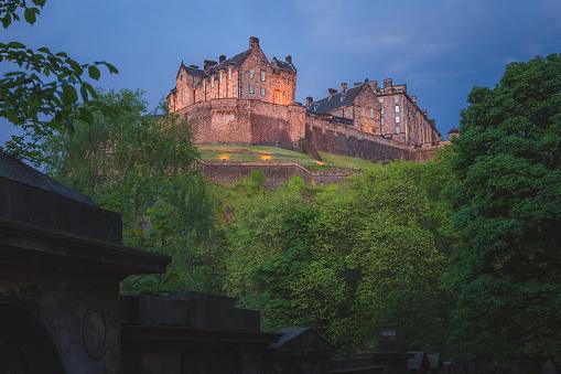 A spooky, moody view of the landmark Edinburgh Castle at night from St Cuthbert cemetery in Edinburgh, Scotland.