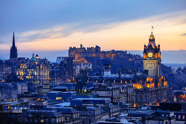 Edinburgh City Skyline After Sunset Looking over the buildings and roofs of Edinburgh Old Town towards Edinburgh Castle from Calton Hill shortly after sunset. An orange glow in the sky and orange building lights stand out against the shadowy city. theasis stock pictures, royalty-free photos & images