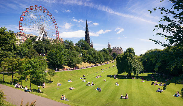 Edinburgh during warm summer weather Princes Street Gardens, in the city centre of Edinburgh, with people relaxing on the lawn and benches at the start of the city's summer festival season. princes street edinburgh stock pictures, royalty-free photos & images