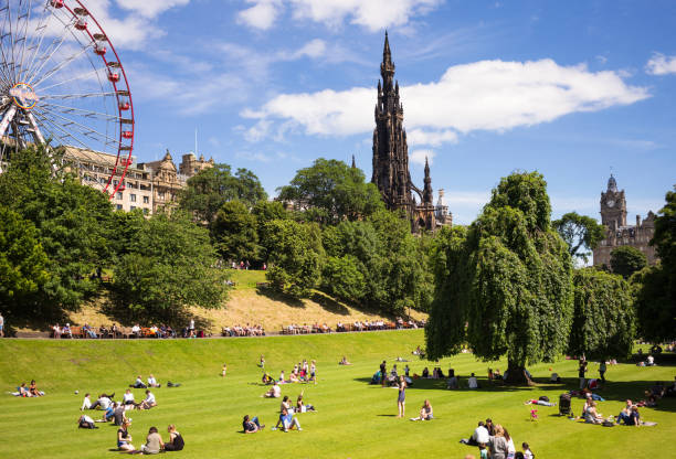 Edinburgh in warm summer weather Edinburgh, Scotland, UK - People sunbathing and relaxing on the lawn in Princes Street Gardens, with the Balmoral Hotel, the Scott Monument, and a ferris wheel attraction on Princes Street. princes street edinburgh stock pictures, royalty-free photos & images