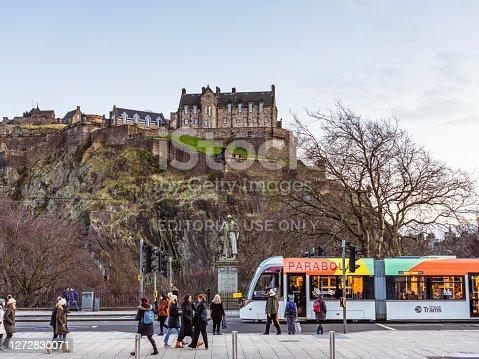 Edinburgh, Scotland - A tram passing as pedestrians walk on Princes Street in central Edinburgh, with the castle on the skyline.