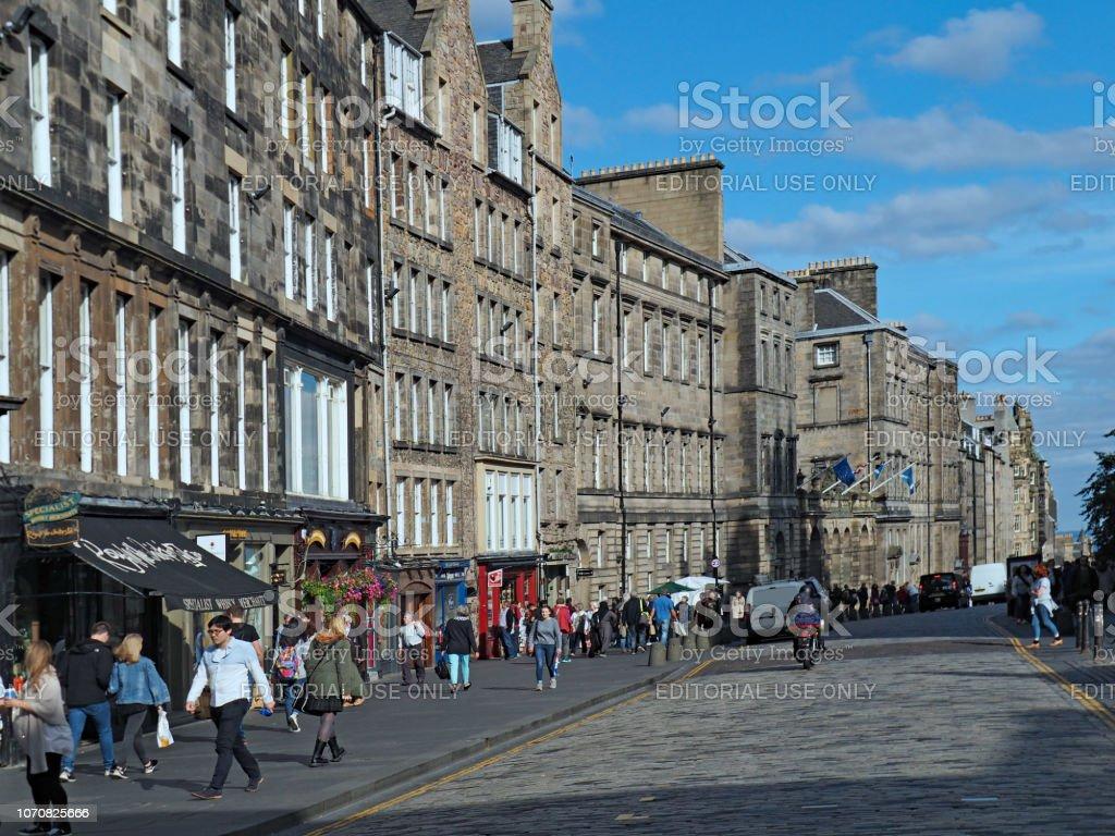 Edinburgh, shoppers walk among the historic buildings of the Royal Mile. stock photo