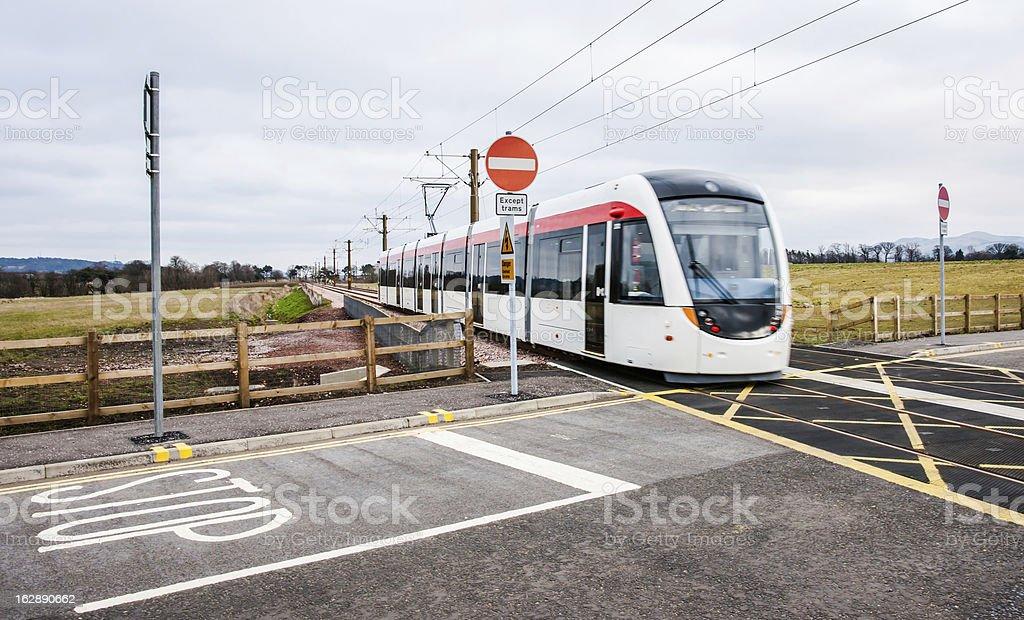 Edinburgh tram passes over unmanned level crossing stock photo