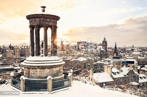 The historic city centre of Edinburgh covered in snow, taken at sunset from Calton Hill in December, with the historic Dugald Stewart Monument in the foreground.