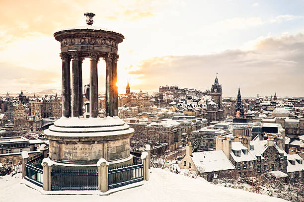 Edinburgh Under Snow The historic city centre of Edinburgh covered in snow, taken at sunset from Calton Hill in December, with the historic Dugald Stewart Monument in the foreground. edinburgh scotland stock pictures, royalty-free photos & images