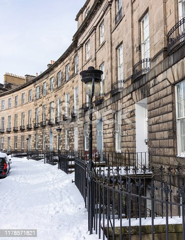 A curving Georgian crescent in the New Town of Edinburgh, with snow covering the pavement.