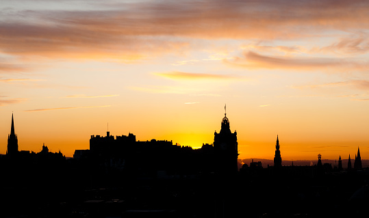 Key landmarks of the Scottish capital Edinburgh, silhouetted against an autumn sunset.