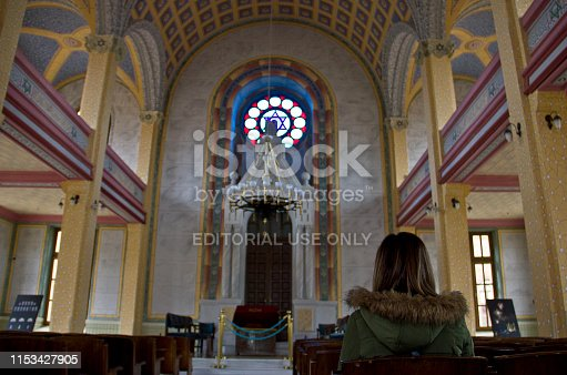 Edirne, Turkey - April 19, 2019: Young woman in Edirne Synagogue, is an abandoned synagogue located in Maarif Cd, 10 in Edirne, Turkey. The synagogue was built in 1907 by the architectural model of Leopoldstȁdter Tempel in Vienna. The synagogue was in use until 1983 and could accommodate 1,200 worshipers, 900 men and 300 women.