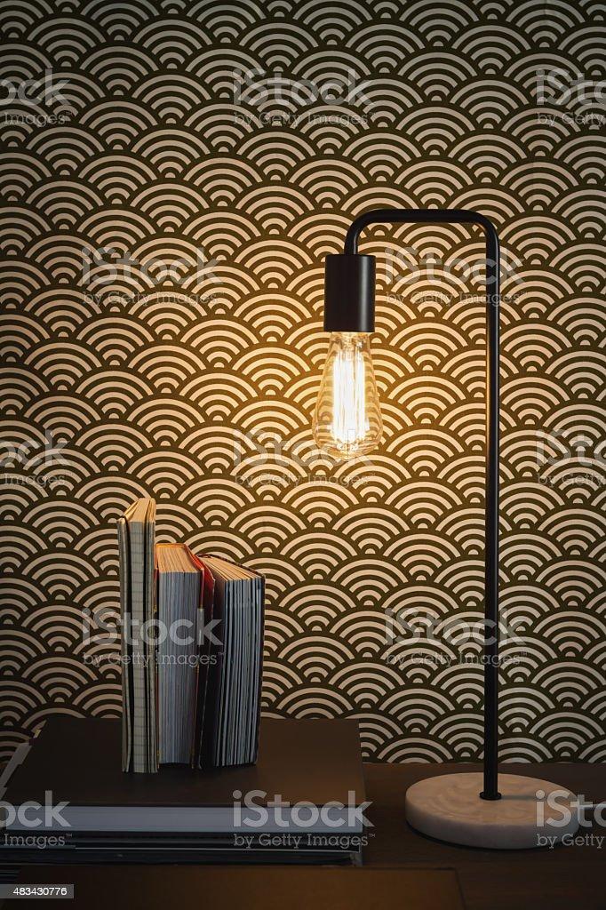 Edison filament table lamp and books home interior stock photo