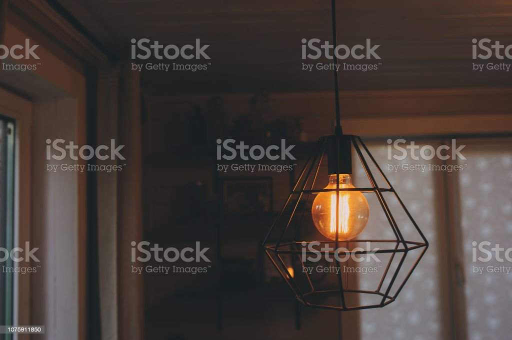 edison lamp in vintage style lighting in evening home interior. Earth...