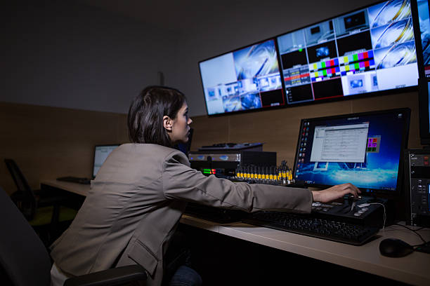 TV editor working with vision mixer in television broadcast gallery stock photo