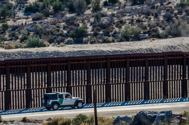 Editorial December 3, 2015: US - Mexico Border Border fence between Mexico and United States in the California desert near Jacumba. international border barrier stock pictures, royalty-free photos & images