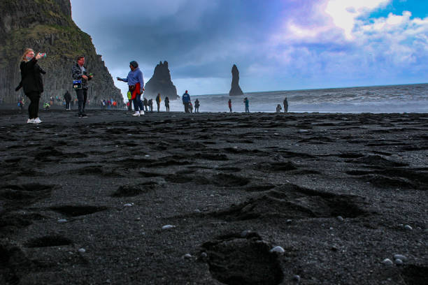 Editorial photo of touristsexploring the black sand beach of vik. This beach is known for its beauty, and large dangerous waves. Tourists have died from getting to close to water stock photo