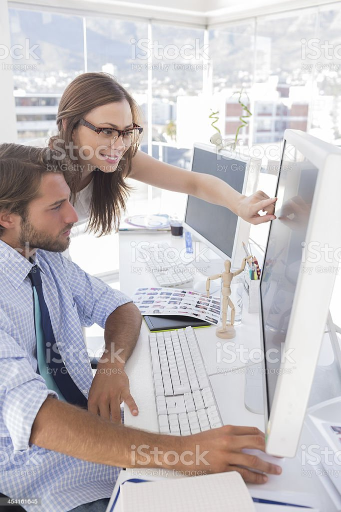 Editors reviewing photographs on computer royalty-free stock photo