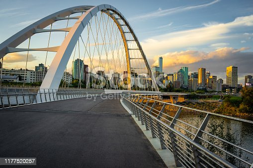 View of Edmonton, Albert, Canada skyline seen from suspension bridge with walking path and river in the foreground shot at dusk with partially cloudy sky
