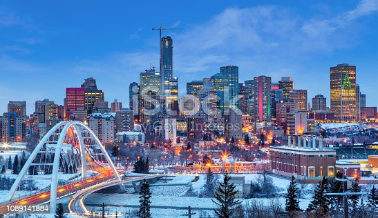 Edmonton downtown Winter skyline just after sunset at the blue hour showing Walterdale Bridge across the frozen, snow-covered Saskatchewan River and surrounding skyscrapers. Edmonton is the capital of Alberta, Canada.